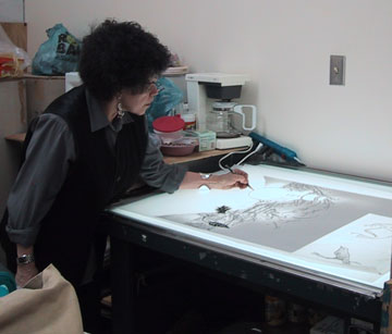 Artist Phyllis Bramson draws her print on an illuminated table.