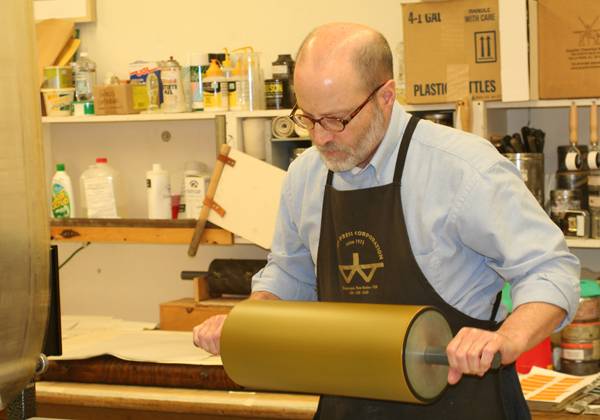 Artist Richard Finch uses a print roller in the studio.