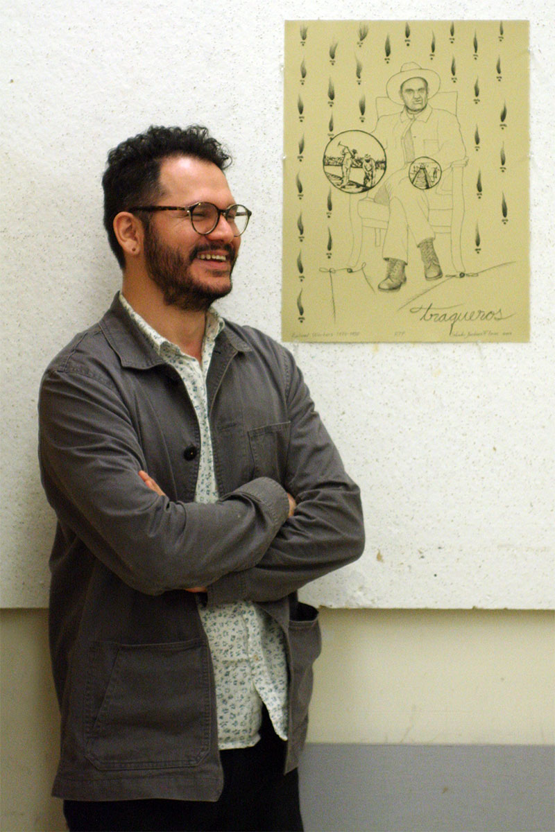 Salvador Jimenez-Flores standing by his print, hanging on a wall.