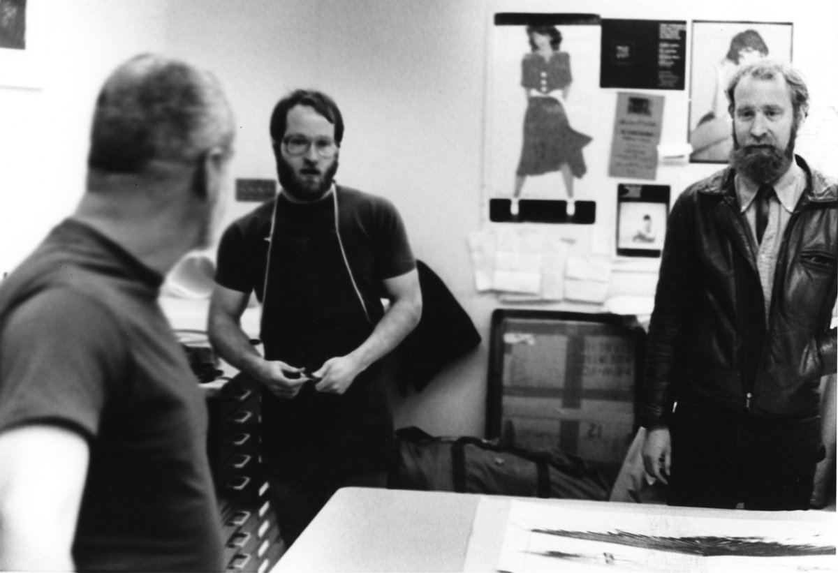 Artist Robert Stackhouse stands with artists Ray George and Richard Finch, reviewing prints laying on a table in front of them.